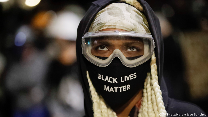 A person wears a Black Lives Matter face mask and goggles