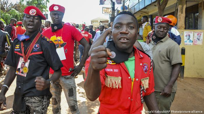 Supporters of Ugandan opposition leader Bobi Wine stand around on the road