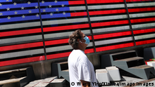 A person wearing a mask walks past a US flag