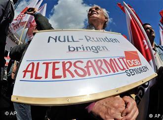 صحنهای از تظاهرات روز کارگر در آلمان. بر روی این پلاکات با خط قرمز نوشته شده: فقر در دوران پیری
