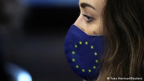 A woman wearing a face mask with the stars and blue of the EU flag (Yves Herman/Reuters)