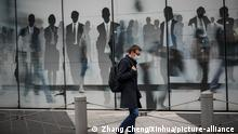 A man wearing a face mask walks on a street in Brussels, Belgium (Zhang Cheng/Xinhua/picture-alliance )