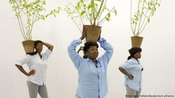 Three women carrying planters on their shoulders or heads
