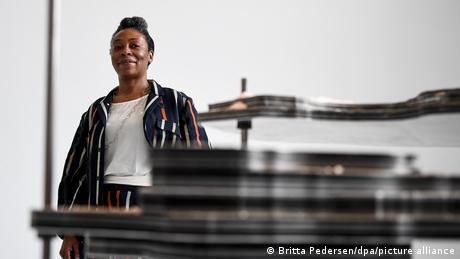 Otobong Nkanga steht hinter ihrer 2015 geschaffenen Skulptur, die einem Schichtmodell ähnelt - Ausstellung There is No Such Thing as Solid Ground - Martin-Gropius-Bau 2020 (Britta Pedersen/dpa/picture alliance)