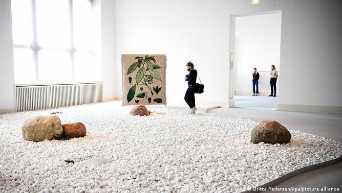 Eine Besucherin läuft durch einen vom weißen Steinen dominierten Raum - Ausstellung der Künstlerin Otobong Nkanga im Martin-Gropius Bau Berlin (Britta Pedersen/dpa/picture alliance)