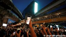 Pro-democracy protesters hold up phones in Bangkok