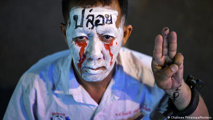 A Thai protester shows the three-finger salute