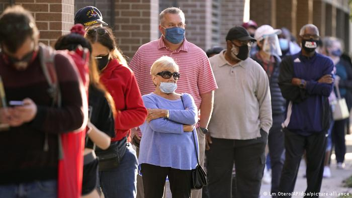 Eleitores americanos usando máscaras de proteção fazem fila durante comparecimento em votação antecipada em Richardson, Texas em 13/10/2020.