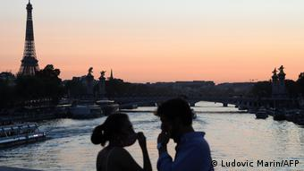 Мужчина и женщина в масках на мосту через Сену на фоне Эйфелевой башни