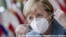 Angela Merkel puts on a face mask (Olivier Hoslet/EPA Pool/dpa/picture-alliance)
