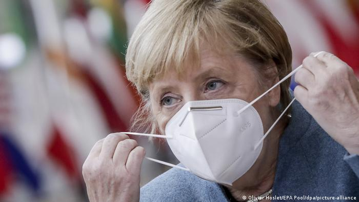 Angela Merkel puts on a face mask