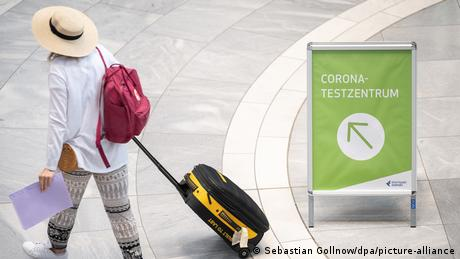 A tourist walks past a sign for a COVID testing facility at Stuttgart airport