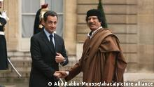Muammar Gaddafi, right, and Nicolas Sarkozy, left, shake hands in 2007