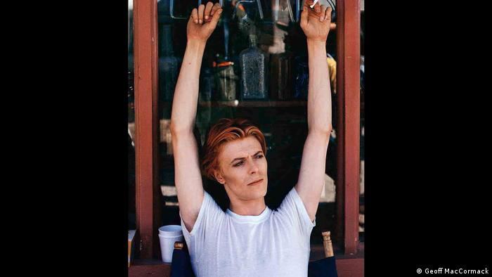 David Bowie holds his arms outstretched on the set of the film The Man Who Fell to Earth in 1976