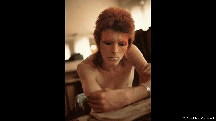 David Bowie reads, looking very concentrated, with his face in make up.
