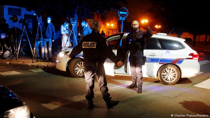 Police officers secure the area near the scene of a stabbing attack in the Paris suburb of Conflans Sainte-Honorine