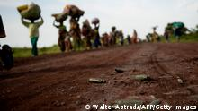 Patronenhülsen liegen auf dem Boden, im Hintergrund gehen Menschen die Gegenstände auf dem Kopf tragen (Walter Astrada/AFP/Getty Images)