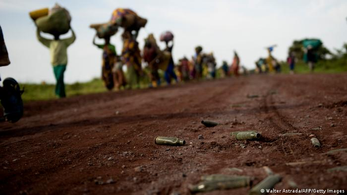 People walk along a dirt road with their belongs balanced on their heads: in the picture foreground is a shell casing