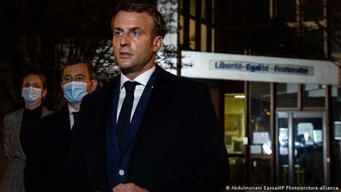 Presidente da França, Emmanuel Macron, em rua à noite, ladeado por homens de máscara protetora