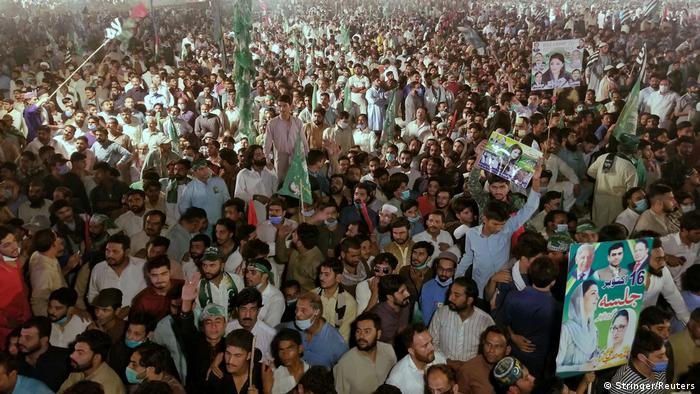 Supporters of Pakistan Democratic Movement (PDM), an alliance of political opposition parties, waves signs as they listen to their leaders during an anti-government protest rally in Gujranwala, Pakistan, October 16, 2020