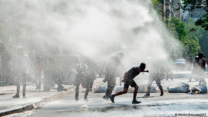 Foto de manifestantes bajo chorros de agua en la Plaza Italia