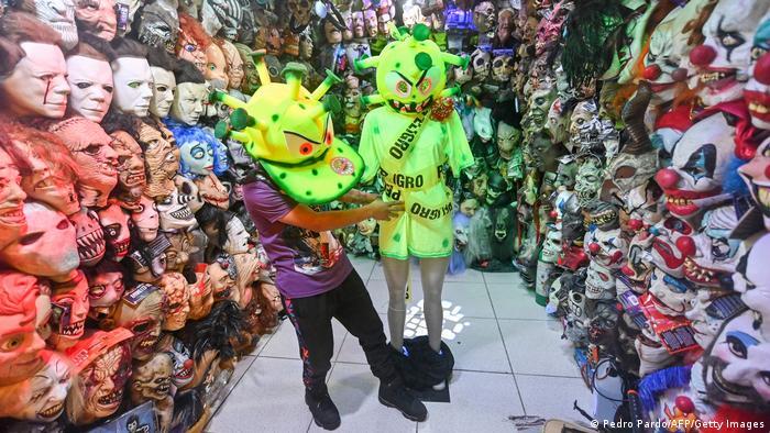 جشن هالووین که در سراسر جهان محبوبیت زیادی دارد، در راه است؛ اگر چه در دوران پاندمی کرونا حال و هوایی این جشن مانند همیشه نخواهد بود. برخی خود را با شیوههای ویژه برای این جشن آماده میکنند و برخی از فروشندگان لباسهای مبدل میکوشند با ابتکارات تازه خود مشتری جلب کنند؛ از جمله این فروشنده در مکزیک که لباسهای کرونایی عرضه میکند.