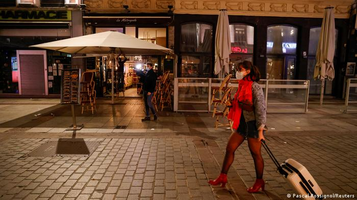 A woman passes by a restaurant during a late-night curfew in Lille, France
