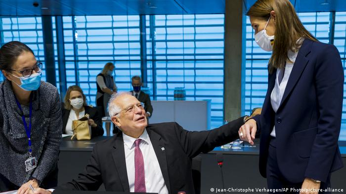 European Union foreign policy chief Josep Borrell, center, speaks with Belgian Foreign Minister Sophie Wilmes, right, during a meeting of European Union foreign ministers at the European Council building in Luxembourg, Monday, Oct. 12, 2020.