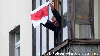 Житель Минска держит бело-красно- белый флаг в знак солидарности с протестующими против Лукашенко