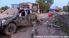 A soldier walks next to a burnt out vehicle