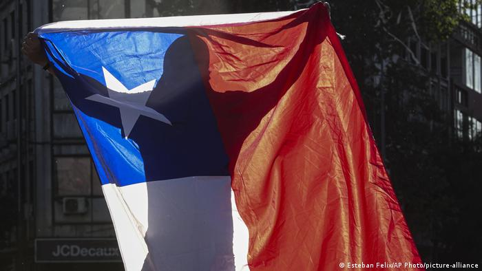 Foto simbólica de una persona manifestante con la bandera de Chile