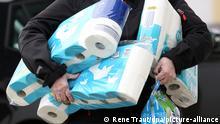 Hamsterkäufe | Siegen: Mann trägt Toilettenpapier und Küchenrolle