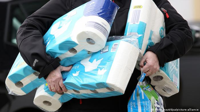 A person carries several packages of toilet paper outside a German supermarket on March 18, 2020