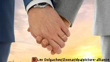 Two men holding hands, wearing wedding band