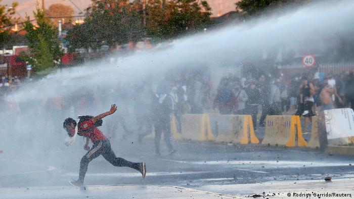 A demonstrator is sprayed by riot police water cannon during a protest against Chile's government