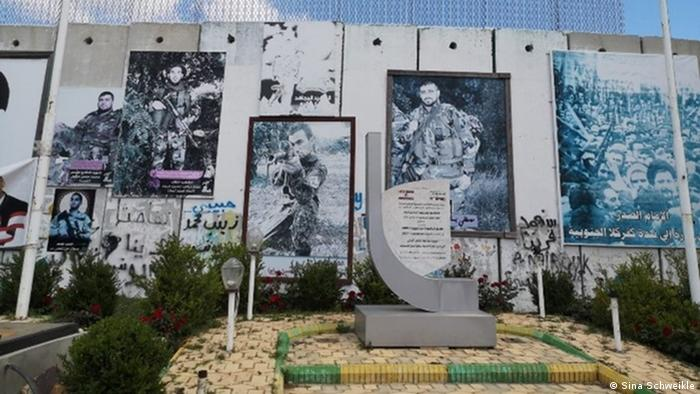 Pictures of men in military fatigues hang from a concrete wall before a stone memorial