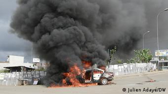 Une voiture brûlée par des manifestants contre un troisième mandat d'Alassane Ouattara à Abidjan, le 19 octobre