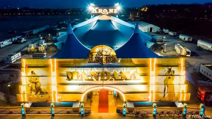 View from above of a large circus tent, lit, that reads Mandana at the front entrance