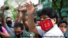 Evo Morales, em meio a apoiadores, usando máscara