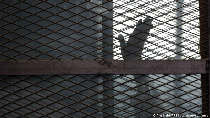 A detainee waves his hand from a defendants cage in a courtroom in Torah prison in Cairo, Egypt