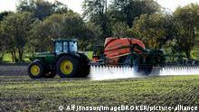 Ein Traktor besprüht ein Feld mit Pestiziden