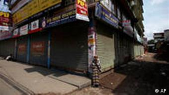 An elderly Nepalese woman stands in front of closed shops in Kathmandu, Nepal, during a general strike called by the Maoists in May
