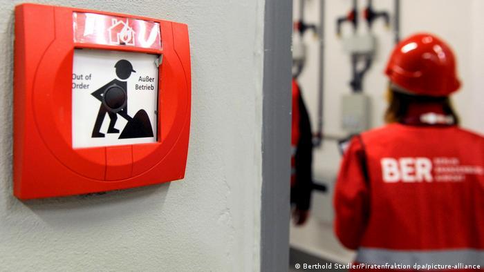 Mulher de veste de segurança escrita BER passa por alarme de incêndio inoperante