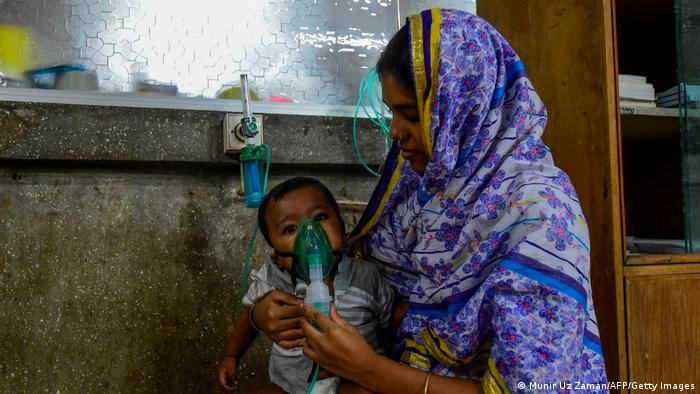 Woman holding a nebulizer on the face of her baby in Bangladesh