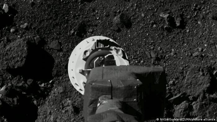 NASAs OSIRIS-REx Sonde berührt mit dem Greifarm den Asteroiden Bennu.