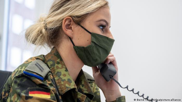 Female Bundeswehr officer on the phone tracing coronavirus outbreaks