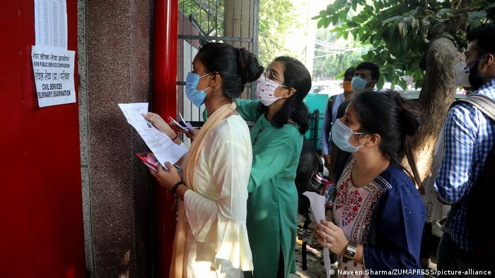 Students wearing face masks are checking for their enrollment numbers at an examination center in New Delhi