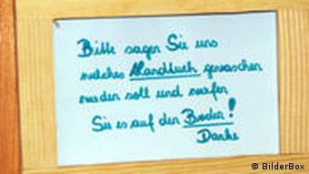 Ein Schild an einer Tür mit der Aufschrift: Bitte sagen Sie uns, welches Handtuch gewaschen werden soll und werfen Sie es auf den Boden. Danke!