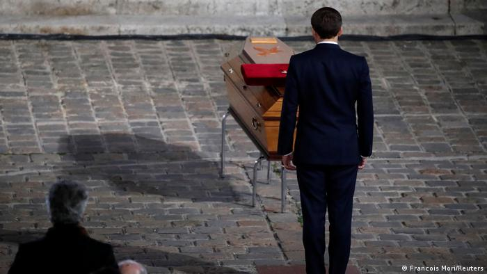 French President Macron standing in front of a casket |