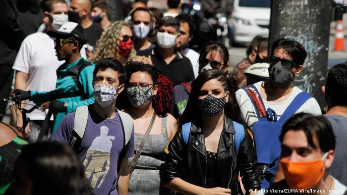 Pessoas caminham em avenida usando máscaras
